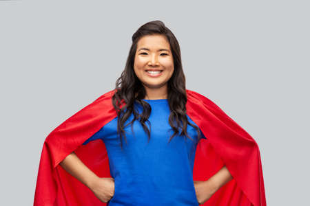 happy asian woman in red superhero cape