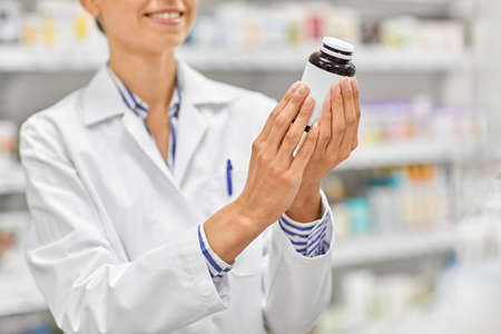 close up of pharmacist with medicine at pharmacy