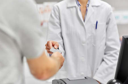 close up of hand giving bank card to pharmacist