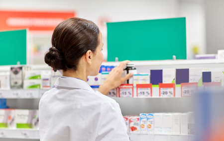 female pharmacist with medicine at pharmacy