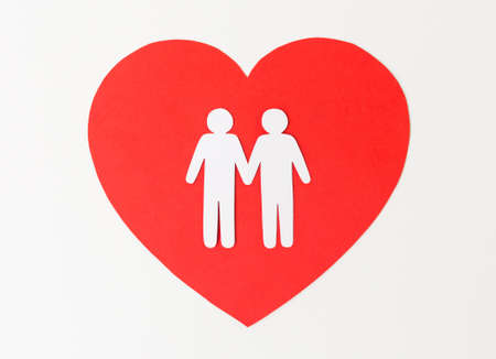 paper cutout of male couple on red heart