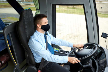 male driver in black mask driving intercity bus