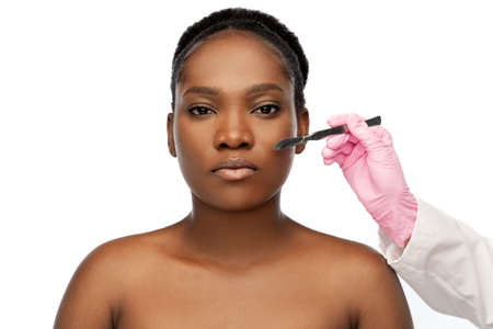 face of african american woman and scalpel knife