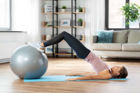 happy woman exercising on fitness ball at home