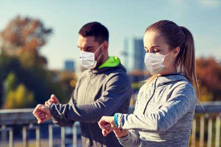 couple in masks running over city highway bridge