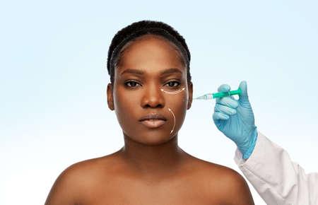 woman and plastic surgeons hand with syringe Standard-Bild