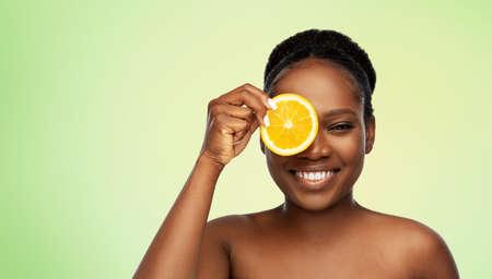 smiling african woman making eye mask of oranges