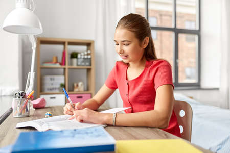 student girl with book writing to notebook at home Standard-Bild