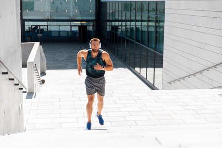 young man in headphones running upstairs outdoors Standard-Bild