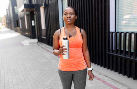 african american woman drinking water after sports