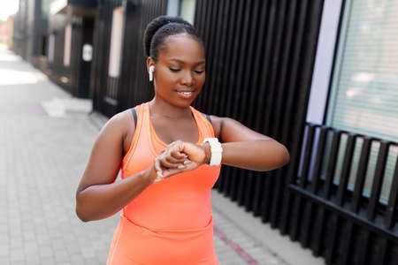 happy african woman with earphones and smart watch