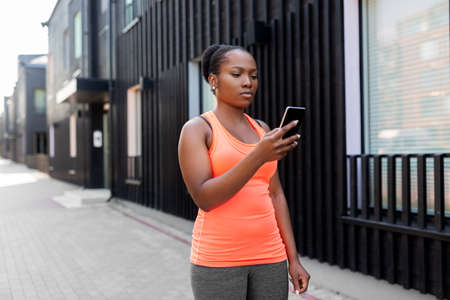 sporty african woman using smartphone in city
