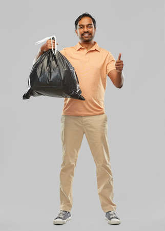 happy indian man with trash bag showing thumbs up Standard-Bild