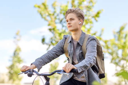 student boy with bag and earphones riding bicycle