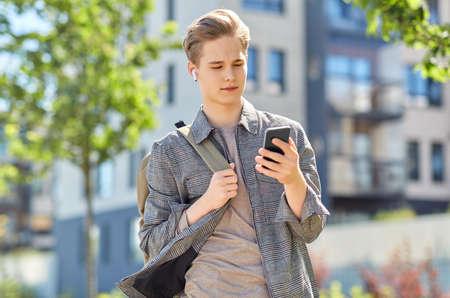 teenage boy with earphones and smartphone in city Standard-Bild
