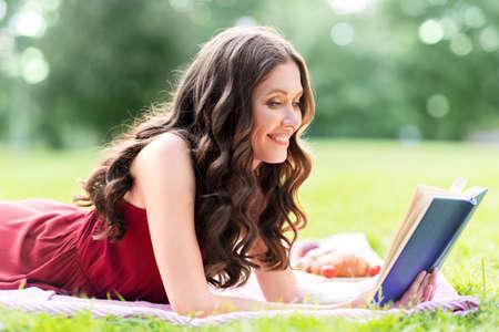 happy smiling woman reading book at summer park Standard-Bild