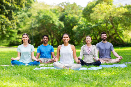 group of happy people doing yoga at summer park