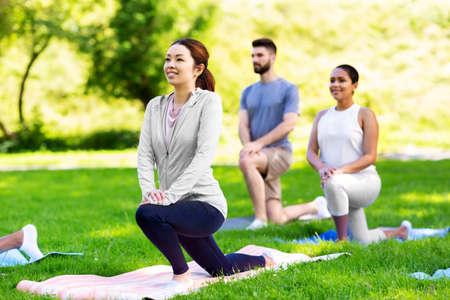 group of people doing yoga at summer park Standard-Bild