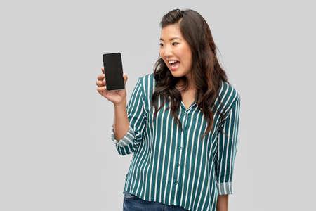 happy asian woman over grey background Standard-Bild