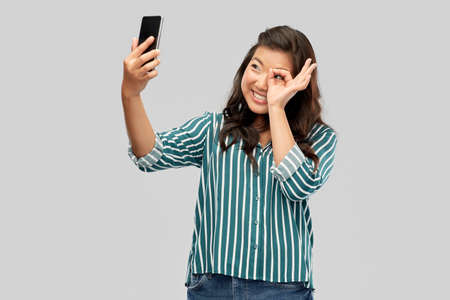 smiling asian woman taking selfie by smartphone