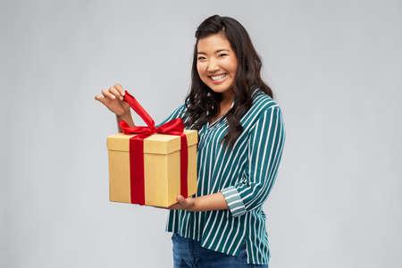 happy asian woman opening gift box