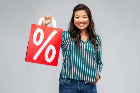 asian woman with percentage sign on shopping bags