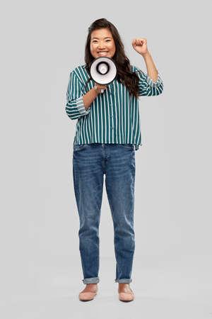 happy smiling asian woman speaking to megaphone Standard-Bild