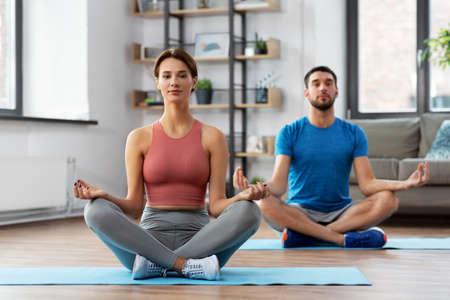 couple meditating in yoga lotus pose at home Standard-Bild