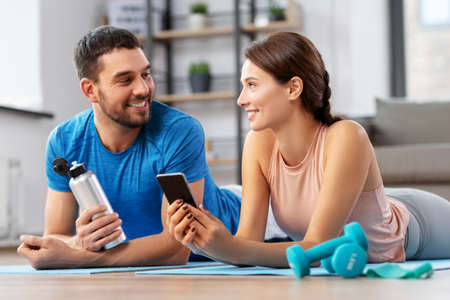 happy couple with smartphone after sports at home