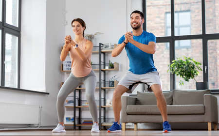 happy couple exercising and doing squats at home Standard-Bild