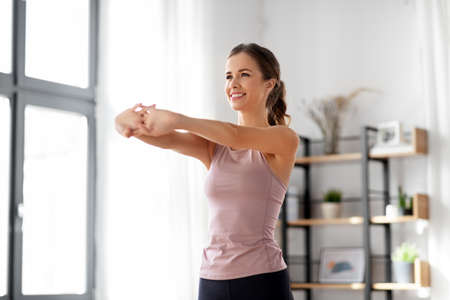 smiling young woman stretching arms at home