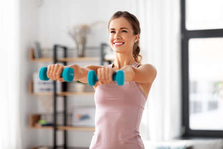 smiling young with dumbbells exercising at home Standard-Bild