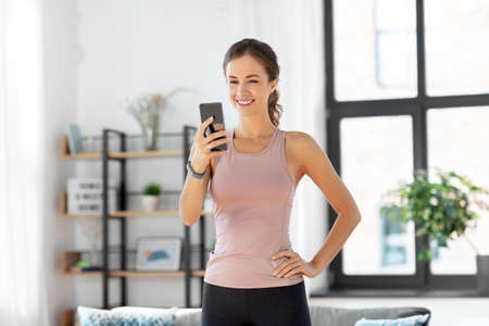 young woman with smatphone exercising at home