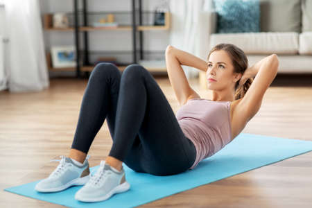 young woman exercising and doing sit-ups at home