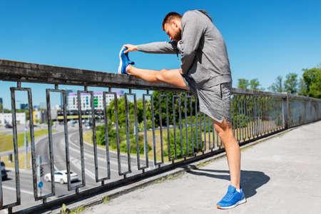 man stretching leg on bridge