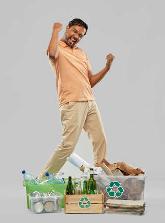 smiling man sorting paper, glass and plastic waste