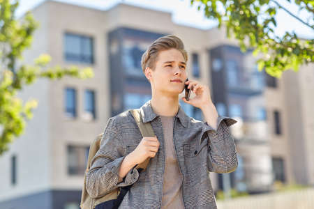 teenage student boy calling on smartphone in city