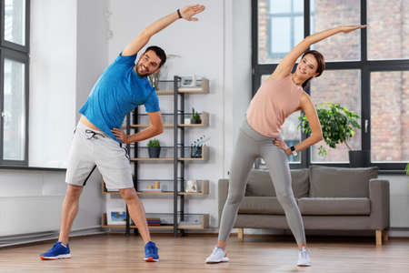 happy couple exercising at home