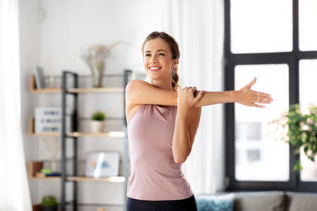 smiling young woman stretching arm at home
