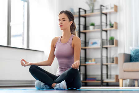 woman doing yoga in lotus pose at home