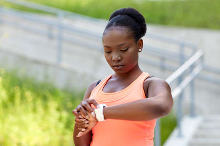 african woman with smart watch doing sports