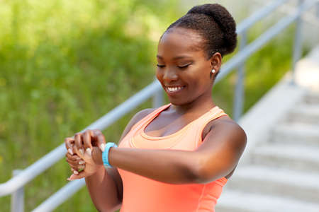 happy african woman with fitness tracker outdoors