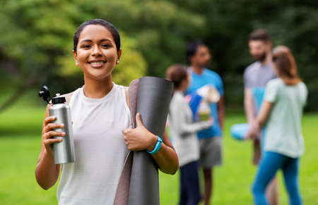 smiling woman with yoga mat and bottle at park Imagens