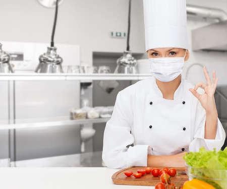 female chef in mask showing ok sign at kitchen Reklamní fotografie