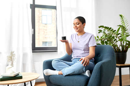 african american woman with smart speaker at home
