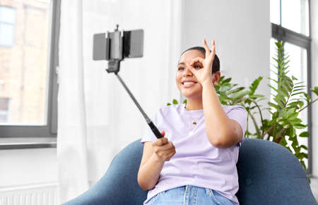 happy african american woman taking selfie at home