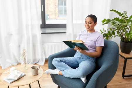 happy african american woman reading book at home