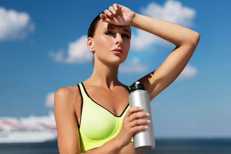 woman drinking water from bottle after sports