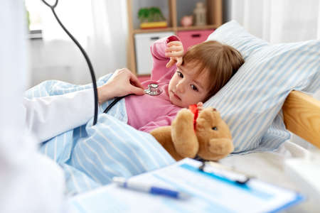 doctor with stethoscope and sick girl in bed