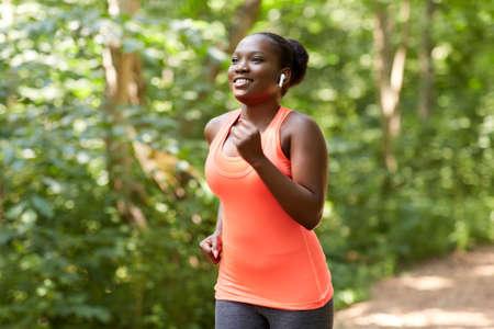 happy african woman in earphones running in park 版權商用圖片